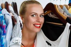 Beautiful smiling blonde woman standing inside wardrobe rack ful Stock Photo