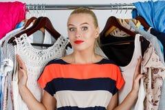Beautiful smiling blonde woman standing inside wardrobe rack ful Stock Photos