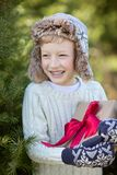 Kid at winter. Beautiful smiling boy in trapper hat and mittens holding christmas gift standing by the tree, winter holiday concept Stock Images