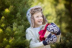 Kid at winter. Beautiful smiling boy in trapper hat and mittens holding christmas gift standing by the tree, winter holiday concept Stock Photos