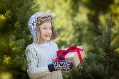 Kid at winter. Beautiful smiling boy in trapper hat and mittens holding christmas gift standing by the tree, winter holiday concept Royalty Free Stock Photo
