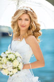 Beautiful smiling bride girl in wedding dress with white umbrell Stock Image