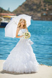 Beautiful smiling bride girl in wedding dress with white umbrell Stock Photography