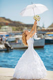 Beautiful smiling bride girl in wedding dress with white umbrell. A and bouquet of flowers walking on seafront, outdoors portrait Stock Images