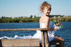 Beautiful smiling bride sitting on the bridge Stock Images