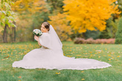 Beautiful smiling bride sitting on grass in park and holding bouquet. Yellow trees at background Royalty Free Stock Photos