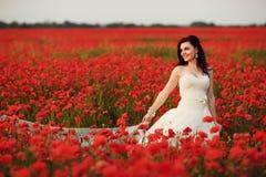 Beautiful smiling bride walking through red poppy fild at sunset Royalty Free Stock Image