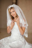 Beautiful smiling bride woman in wedding dress and bridal veil p. Osing in interior. Beauty indoor portrait Royalty Free Stock Photos