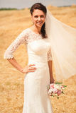 Beautiful smiling bride on yellow field at sunny day Stock Photo