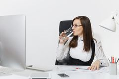 Beautiful business woman in suit and glasses working at computer with documents in light office stock image
