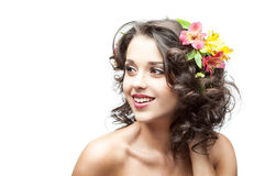 Beautiful smiling brunette girl with flowers in ha. Young attractive caucasian brunette girl with red and yellow flowers in hair which looking away and gently stock image