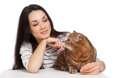 Beautiful smiling brunette girl and her ginger cat over white ba Stock Photo