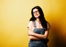 Beautiful smiling brunette girl wearing glasses in denim overall posing beside yellow wall. royalty free stock photo