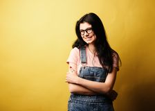Beautiful smiling brunette girl wearing glasses in denim overall posing beside yellow wall. royalty free stock image