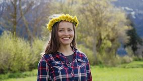 Beautiful smiling brunette girl with a wreath of dandelions on her head on flower field in mountains. Portrait. 4k stock video