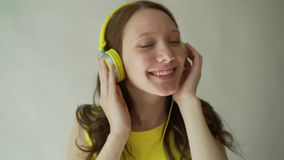 Beautiful Smiling Brunette Listens Music Using Headphones in the Studio on Grey Background. Beautiful Smiling Brunette Listens Music Using Headphones in the stock video footage