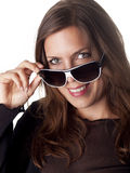 Beautiful smiling brunette looking over her sunglasses Royalty Free Stock Images