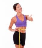 Beautiful smiling brunette measuring her waist Stock Photo