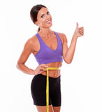 Beautiful smiling brunette measuring her waist Royalty Free Stock Photography