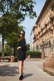 Beautiful and smiling brunette model girl with the trendy backpack in a stylish black dress and in fashionable royalty free stock images