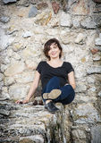 Beautiful smiling brunette posing on the stone wall, beauty and Royalty Free Stock Images