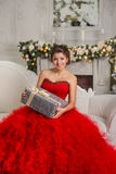 Beautiful smiling brunette sitting on couch holding Christmas gift Royalty Free Stock Photography