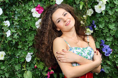 Beautiful smiling brunette woman stands next to green hedge Royalty Free Stock Image