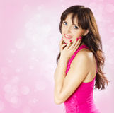 Beautiful smiling brunette woman touching face. Bokeh on pink background Stock Images