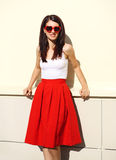 Beautiful smiling brunette woman wearing a red sunglasses and skirt Royalty Free Stock Photography
