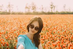 Smiling woman taking a self-portrait in flowers field, pov. stock images