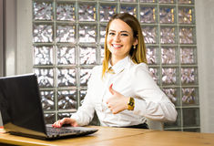 Beautiful smiling business woman showing thumbs up next to her laptop Royalty Free Stock Image