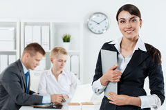 Beautiful smiling business woman in suit holding clipboard in ha Stock Photography