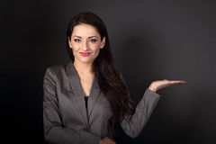 Beautiful smiling business woman in suit holding and presenting Royalty Free Stock Photo