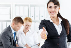 Beautiful smiling business woman in suit offering hand to shake Stock Photos