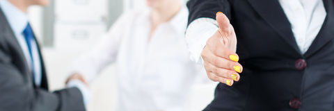 Beautiful smiling business woman in suit offering hand to shake Stock Image