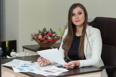 Beautiful smiling business woman working at her office desk with documents. Beautiful smiling business woman working at her office desk with documents Royalty Free Stock Images