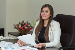 Beautiful smiling business woman working at her office desk with documents. Beautiful smiling business woman working at her office desk with documents Royalty Free Stock Photography