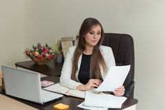 Beautiful smiling business woman working at her office desk with documents. Beautiful smiling business woman working at her office desk with documents Stock Photography