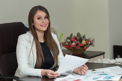 Beautiful smiling business woman working at her office desk with. Documents Royalty Free Stock Images