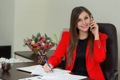 Beautiful smiling business woman working at her office desk with documents and talking on the phone. Beautiful smiling business woman working at her office desk Stock Photo