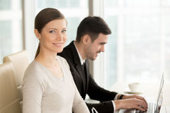 Beautiful smiling businesswoman built successful career posing a. T workplace with laptop near colleague, ambitious lady looking at camera in office, powerful Royalty Free Stock Image
