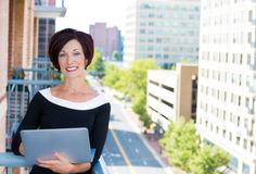 Beautiful smiling businesswoman, customer service representative or a student, checking her e-mail on a laptop Stock Image