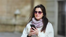 Beautiful smiling businesswoman enjoying break using smartphone outdoor at sunny day medium close-up. Casual happy pretty girl walking typing message using stock video