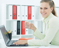 Beautiful smiling businesswoman holding glass of water in hand. Royalty Free Stock Images