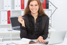 Beautiful smiling businesswoman holding pen in hand looking straight to the camera. Stock Photography