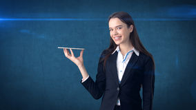 Beautiful smiling businesswoman is holding the tray and looking at something Stock Photography
