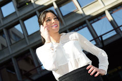 Beautiful smiling businesswoman on the phone in a office buildin Royalty Free Stock Images