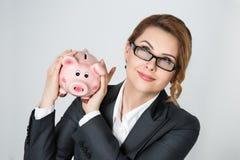 Beautiful smiling businesswoman shaking piggy bank Stock Images