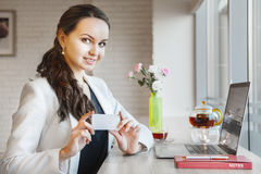 Beautiful smiling businesswoman and showing business card in her hands Stock Photography