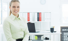 Beautiful smiling businesswoman sitting on the background of her office. Stock Images